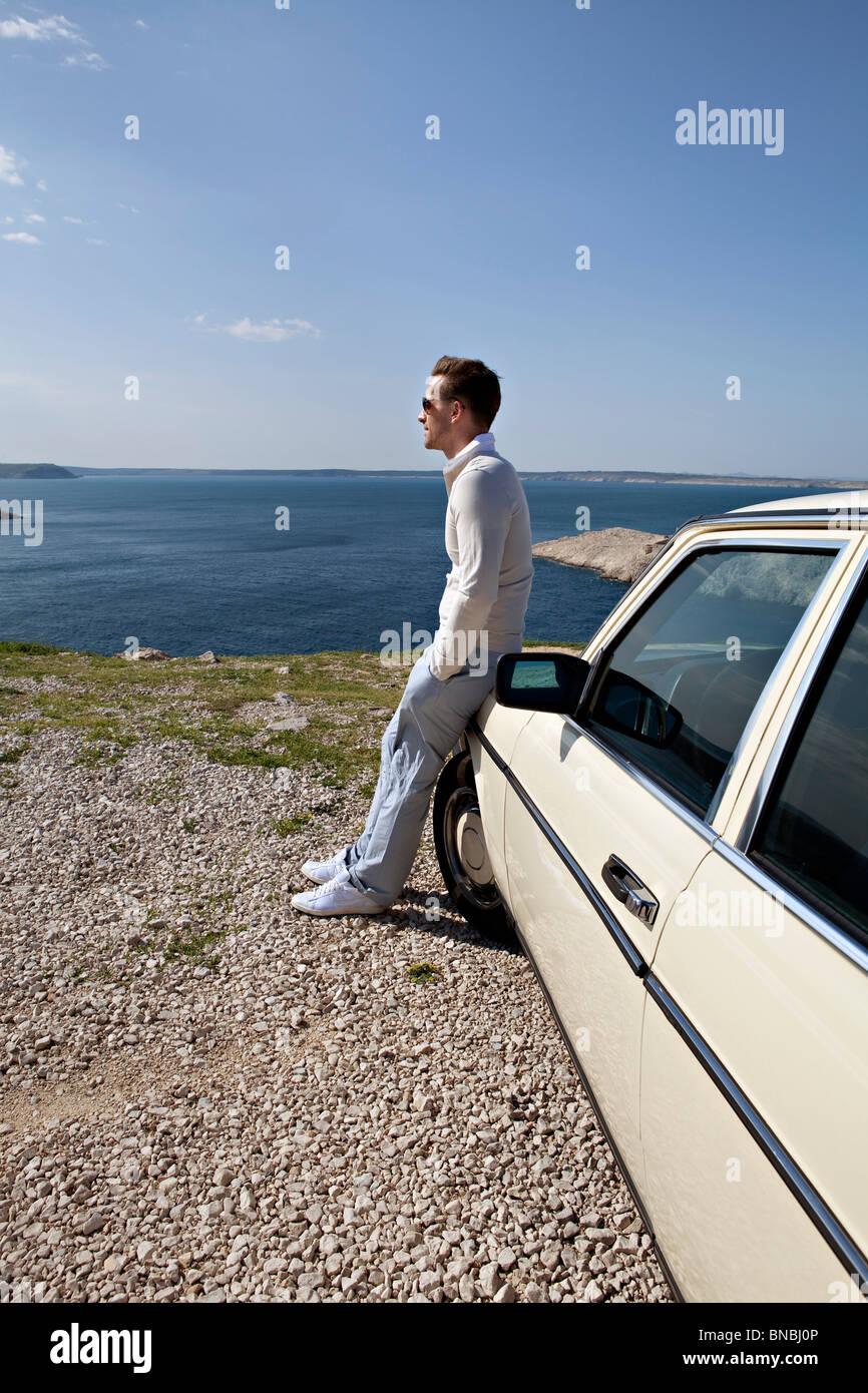 Mann mit Oldtimer mit Blick auf Meer Stockbild
