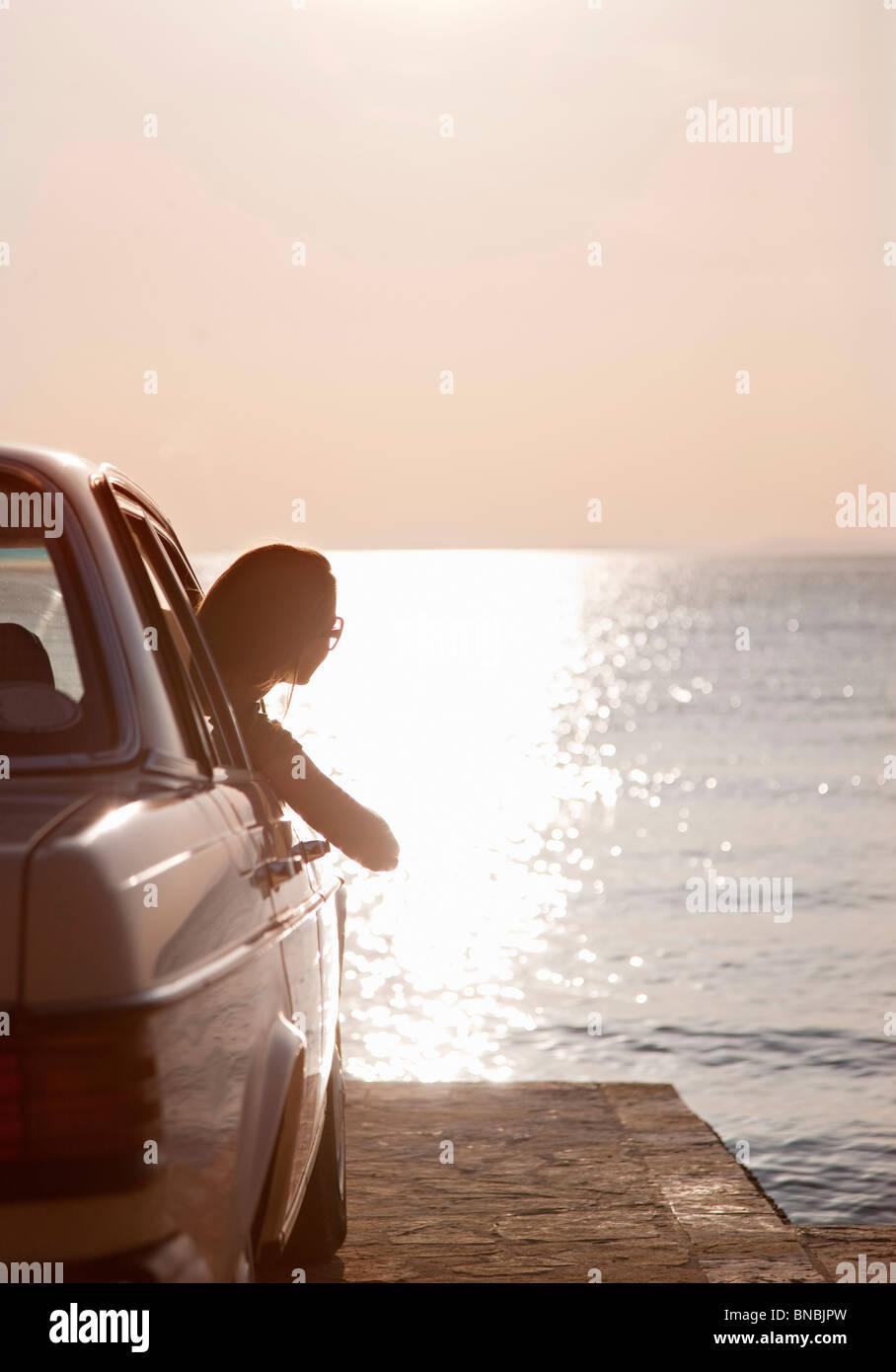 Frau mit Oldtimer auf dem Seeweg Stockbild