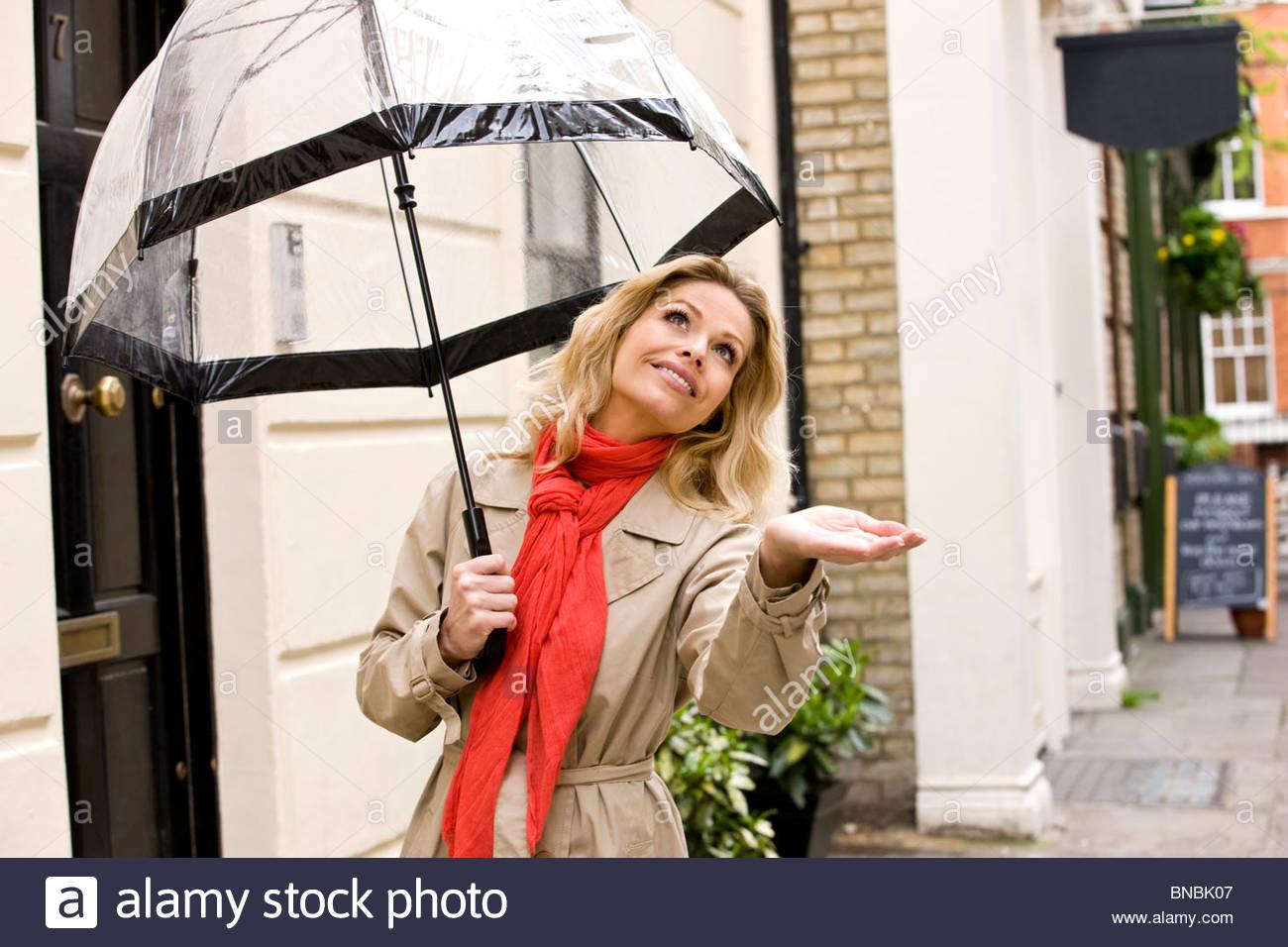 Eine Mitte Erwachsene Frau mit Regenschirm, Regen wird gesucht Stockbild