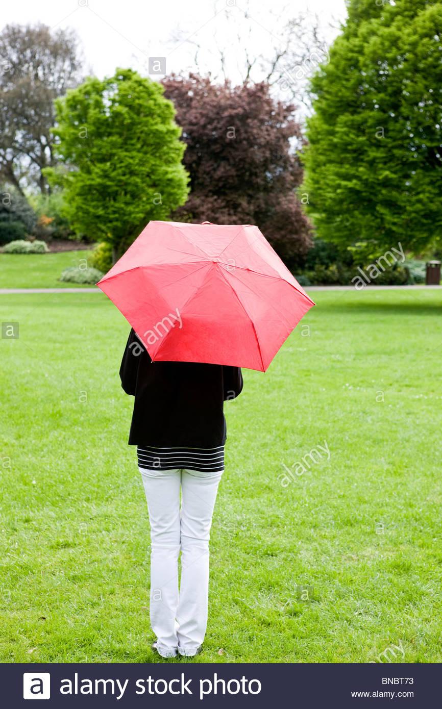 Eine Frau steht in einem Park, mit einem roten Regenschirm Rückansicht Stockbild