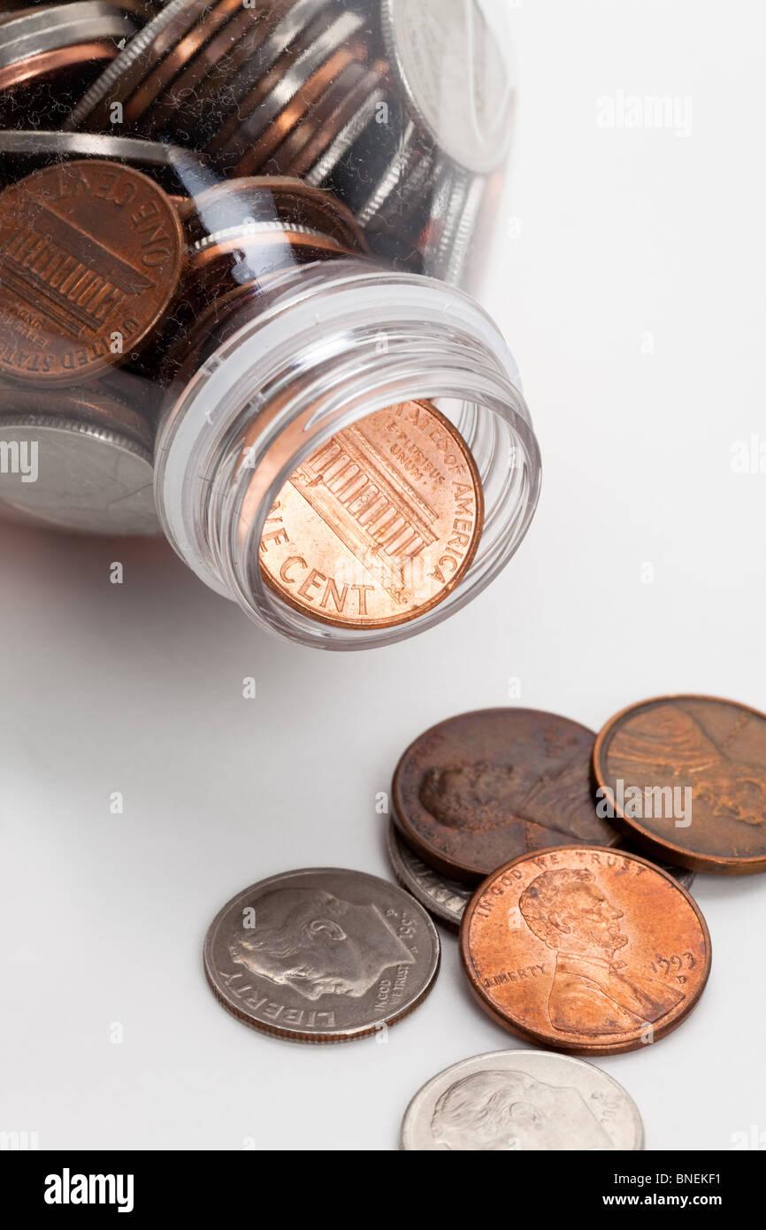 Kunststoff-Flasche und Münzen, Dollar mit weißem Hintergrund Stockbild