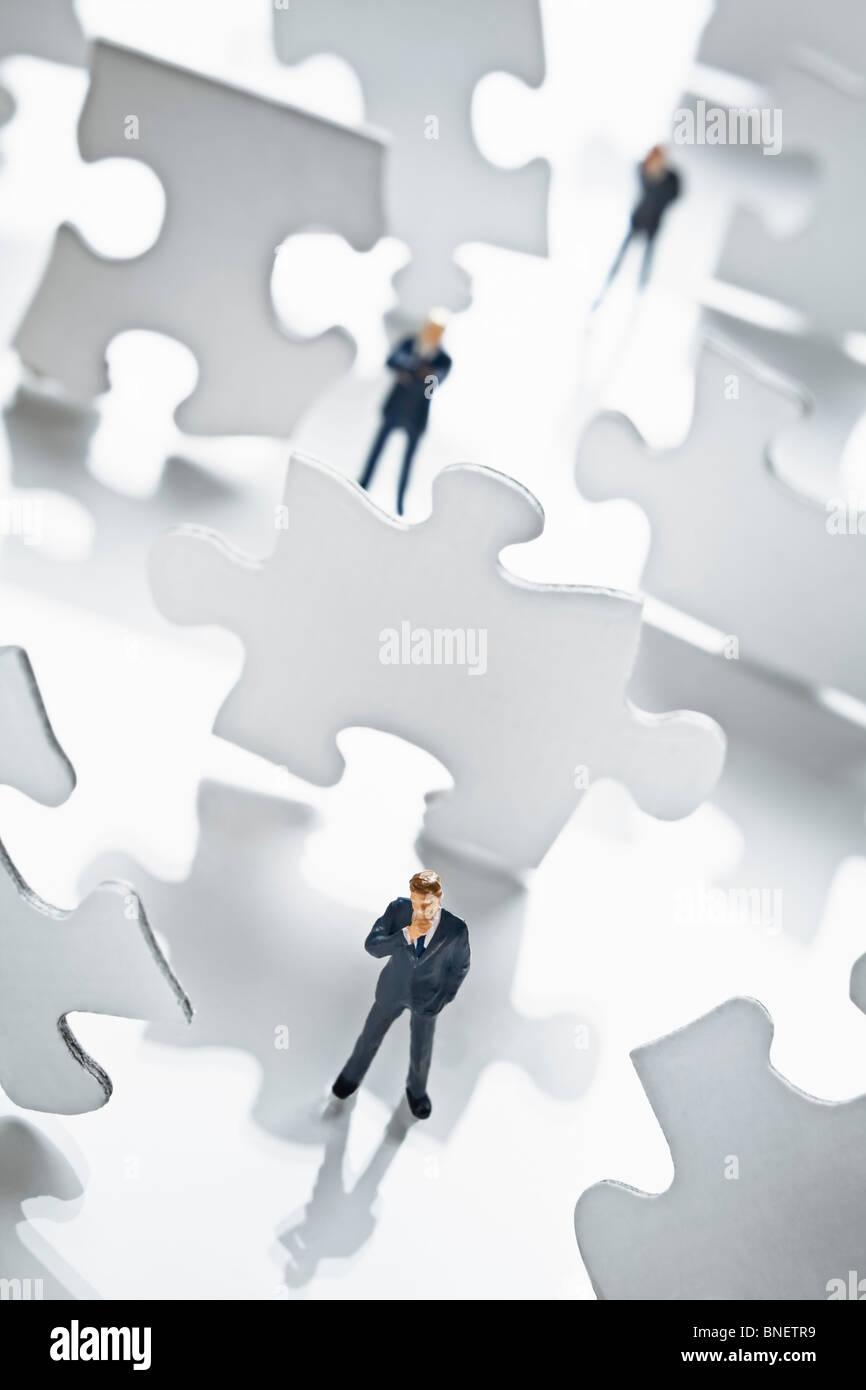 Geschäftsmann Figur umgeben von Puzzle-Teile Stockbild