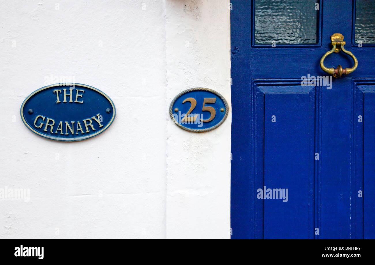 Cast Iron Hausnamen und Nummernschilder an weiß getünchten Wand und eine blaue Haustür mit Messing Stockbild
