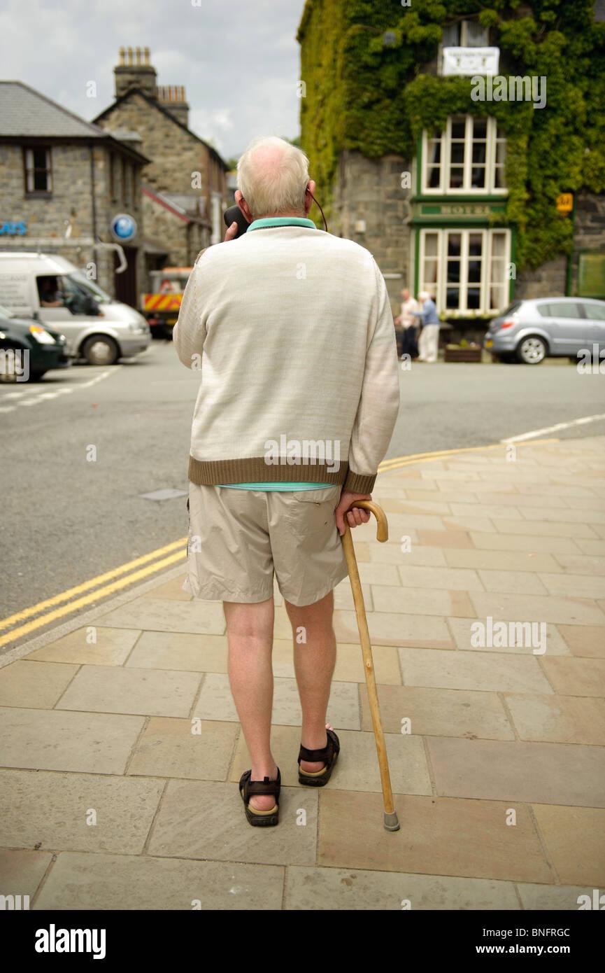 Rückansicht eines älteren Mannes zu Fuß mit Hilfe eines Stockes in Wales, UK Stockbild