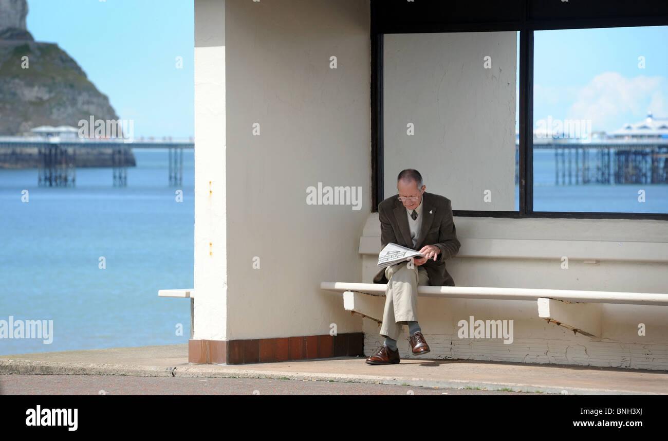 Lesen eine Zeitung auf der Strandpromenade von einem britischen Badeort, UK Rentner. Stockbild