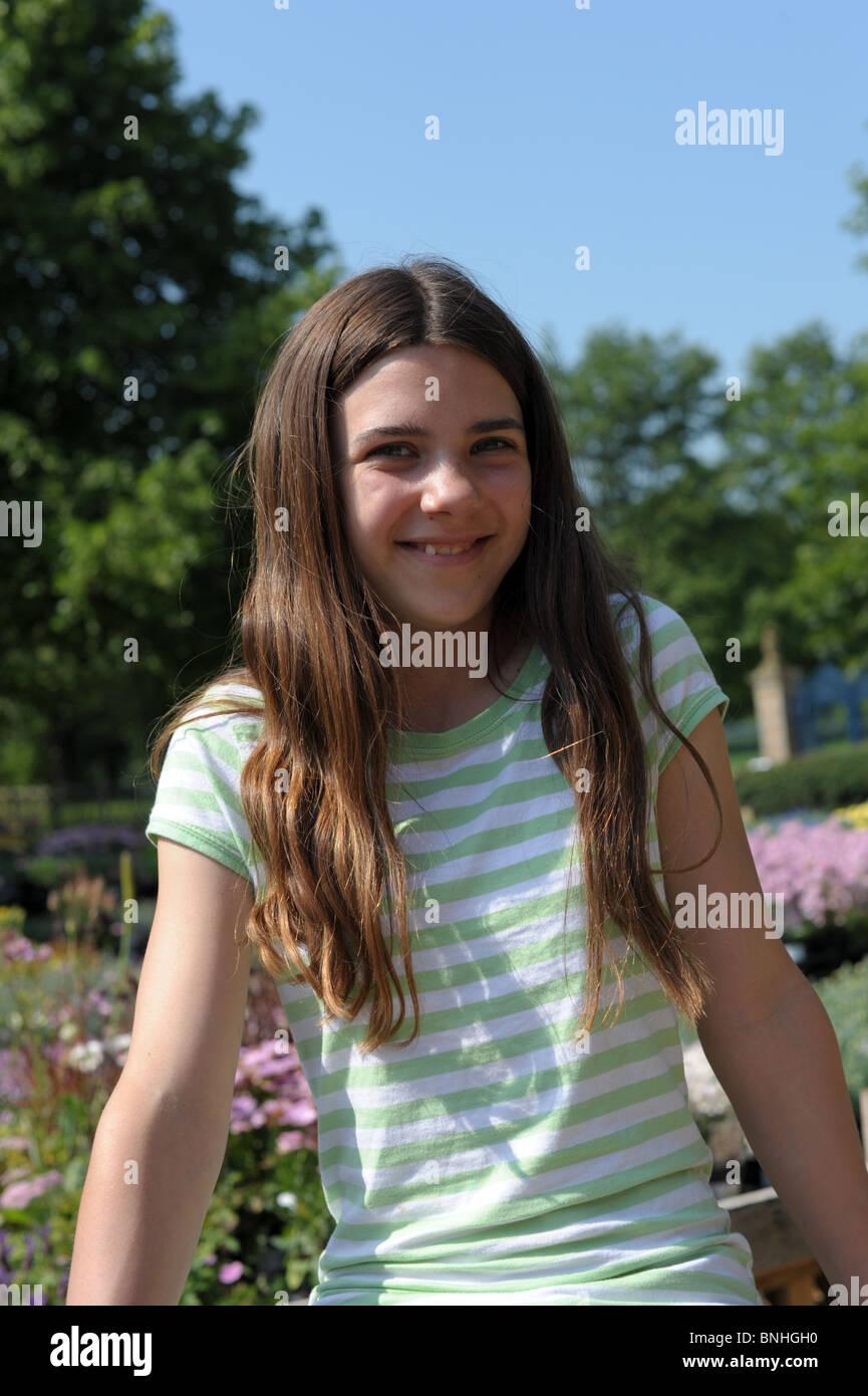 Porträt von ein glücklich lächelndes hübsches junges Mädchen mit langen, dunklen  Haaren sitzen in der Sonne in einem Park mit Blumen a78053f125