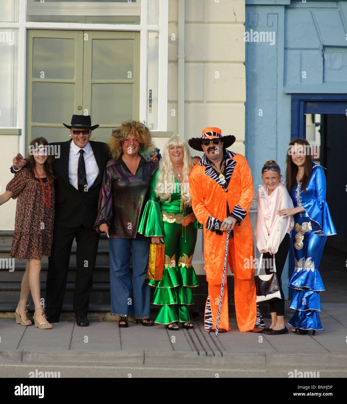 Eine Familie verkleidet für eine 70er Jahre Dekade unter dem Motto Geburtstagsparty, UK Stockbild