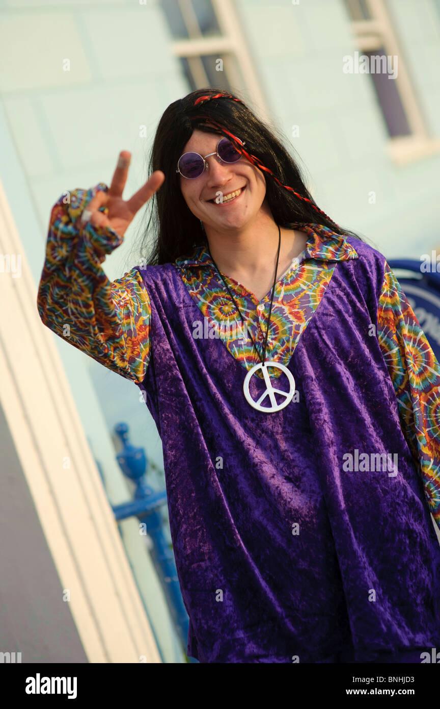 Ein Mann mit Peace-Zeichen als Hippie verkleidet, für eine 70er Jahre Dekade unter dem Motto Geburtstagsparty, Stockbild