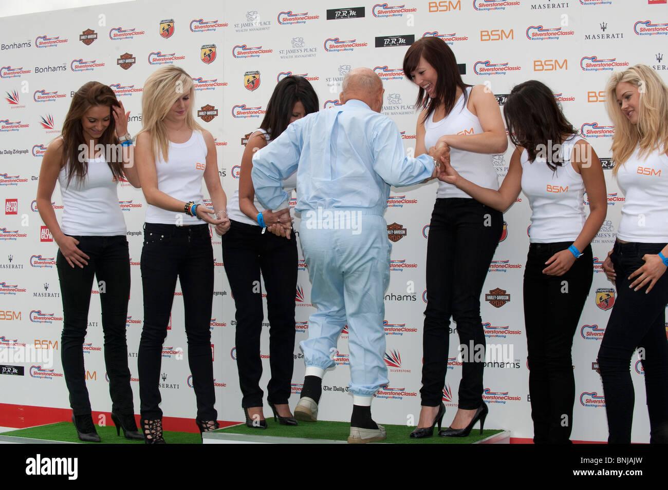 Rennfahrer Sir Stirling Moss mit BSM Aktionen Mädchen bei der Silverstone Classic 2010-Motorsport-Veranstaltung Stockbild