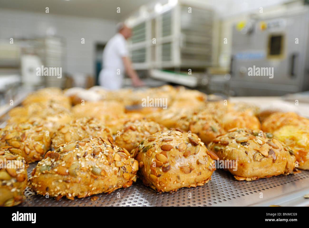 fertige Brötchen vor, verschwommene arbeiten Bäcker hinter Stockbild