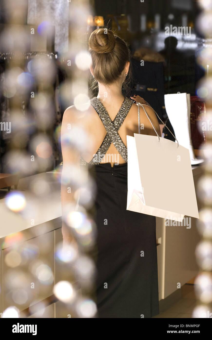 Rückseite des schönen reiche Dame in der boutique Stockfoto