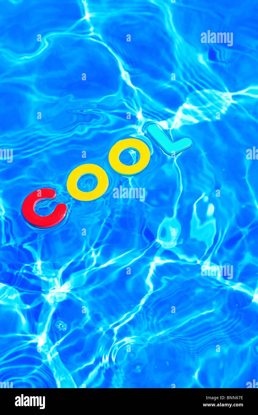 Das Wort COOL aus Schaum Buchstaben schwimmt auf der Wasseroberfläche eines Schwimmbades hergestellt Stockbild