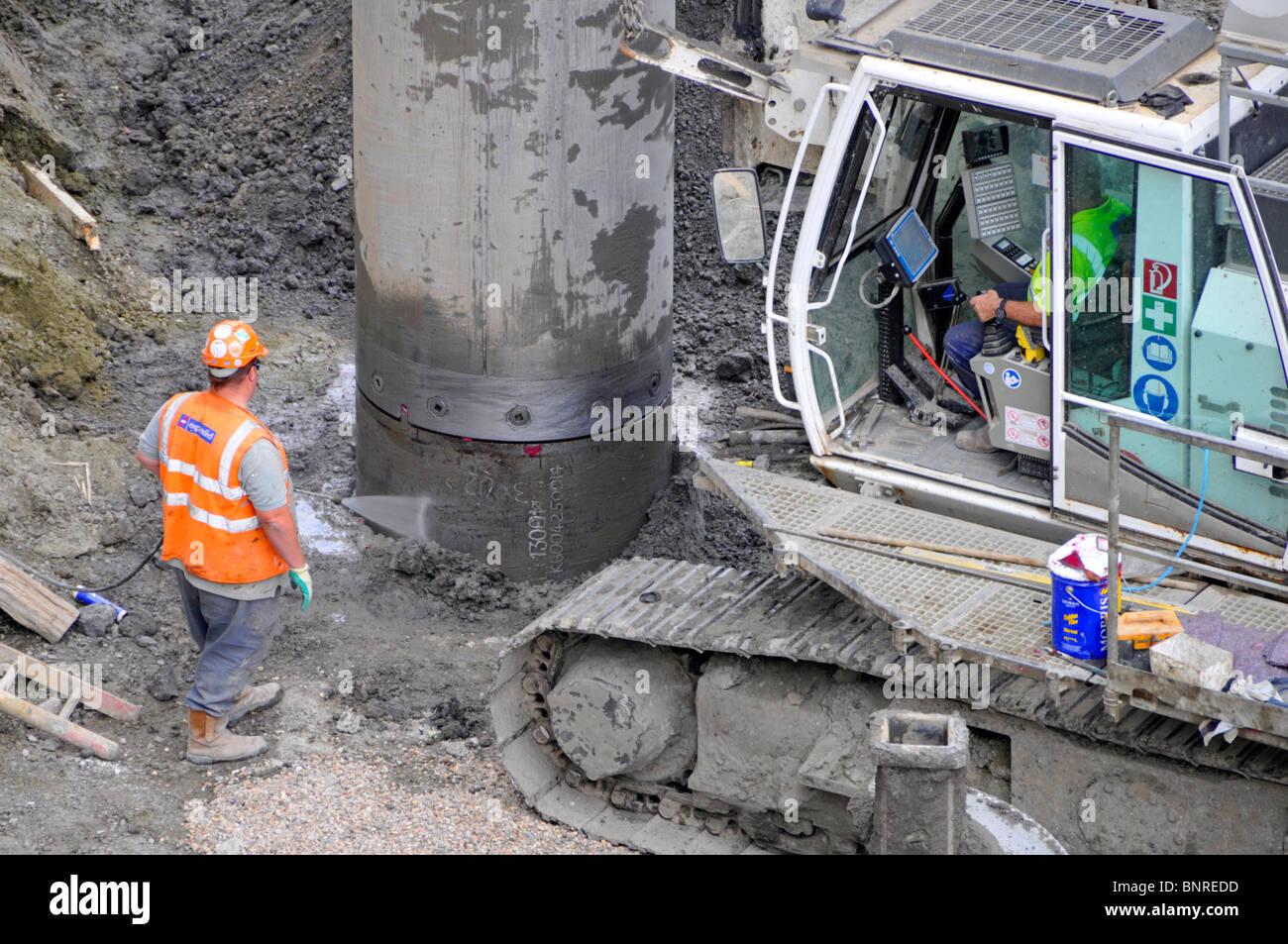 Arbeiter, die Kastration Wasser auf Stahlgehäuse während häufen Arbeit für Stiftungen auf Crossrail Stockbild