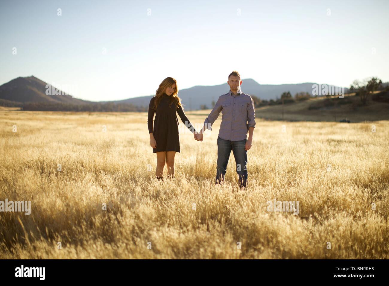 Paar an den Händen halten, als die Kamera schauen und Lächeln in ein offenes Feld Stockbild