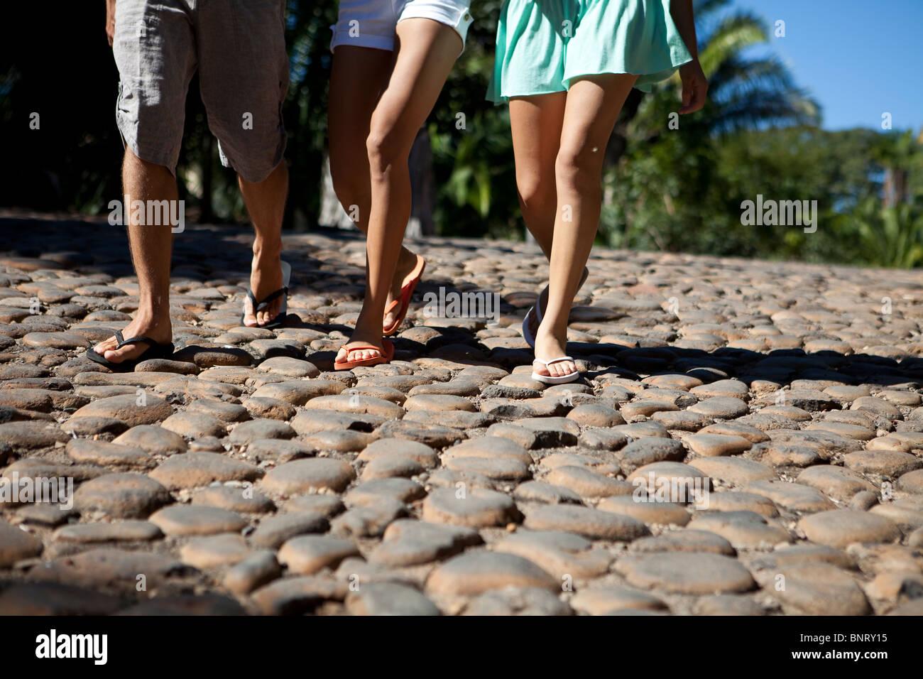 Drei junge Erwachsene schlendern Sie durch eine sonnige Kopfsteinpflaster Straße. Stockbild