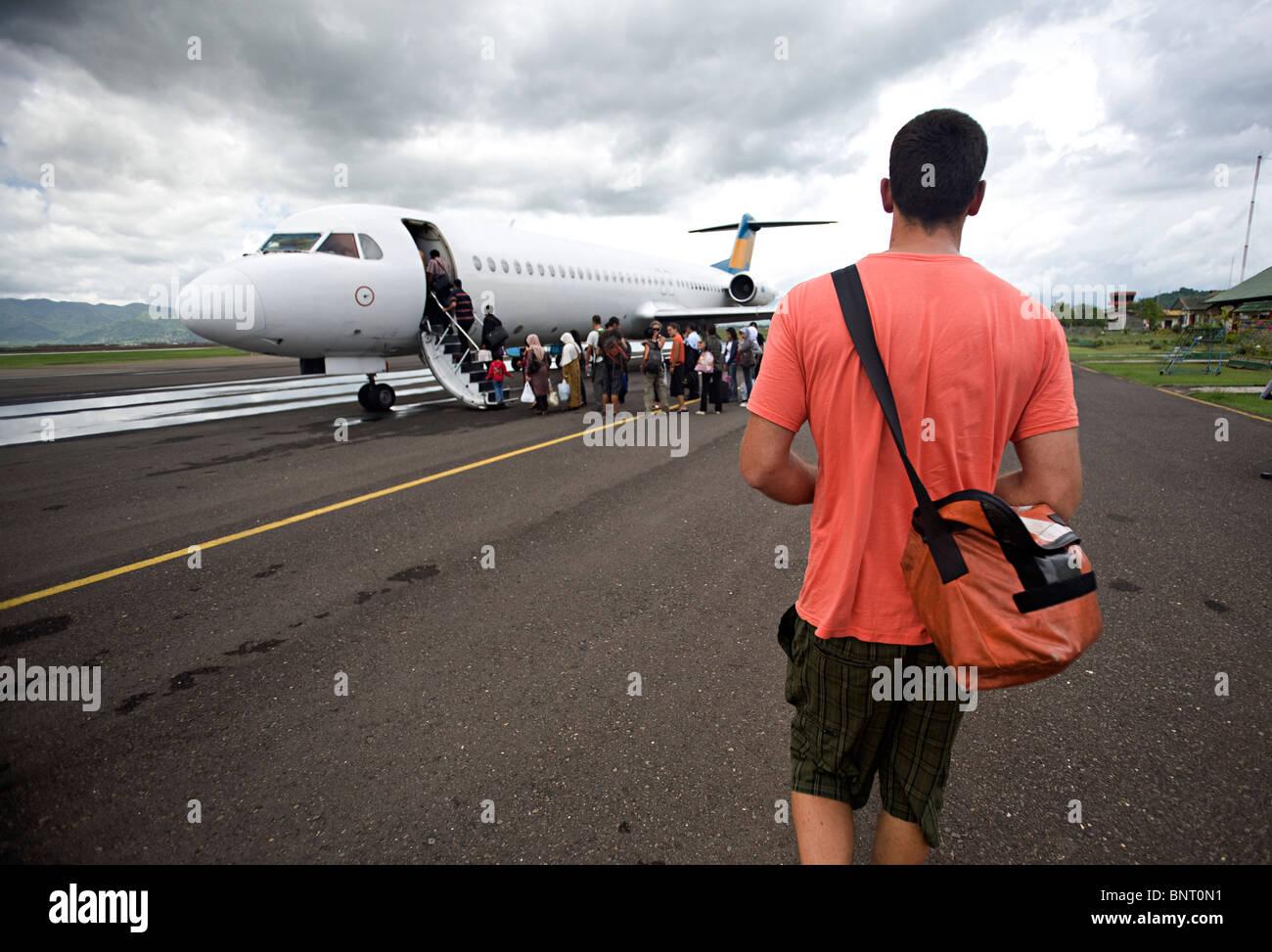 Großer Mann mit Schultertasche geht zum Flugzeug. Stockbild