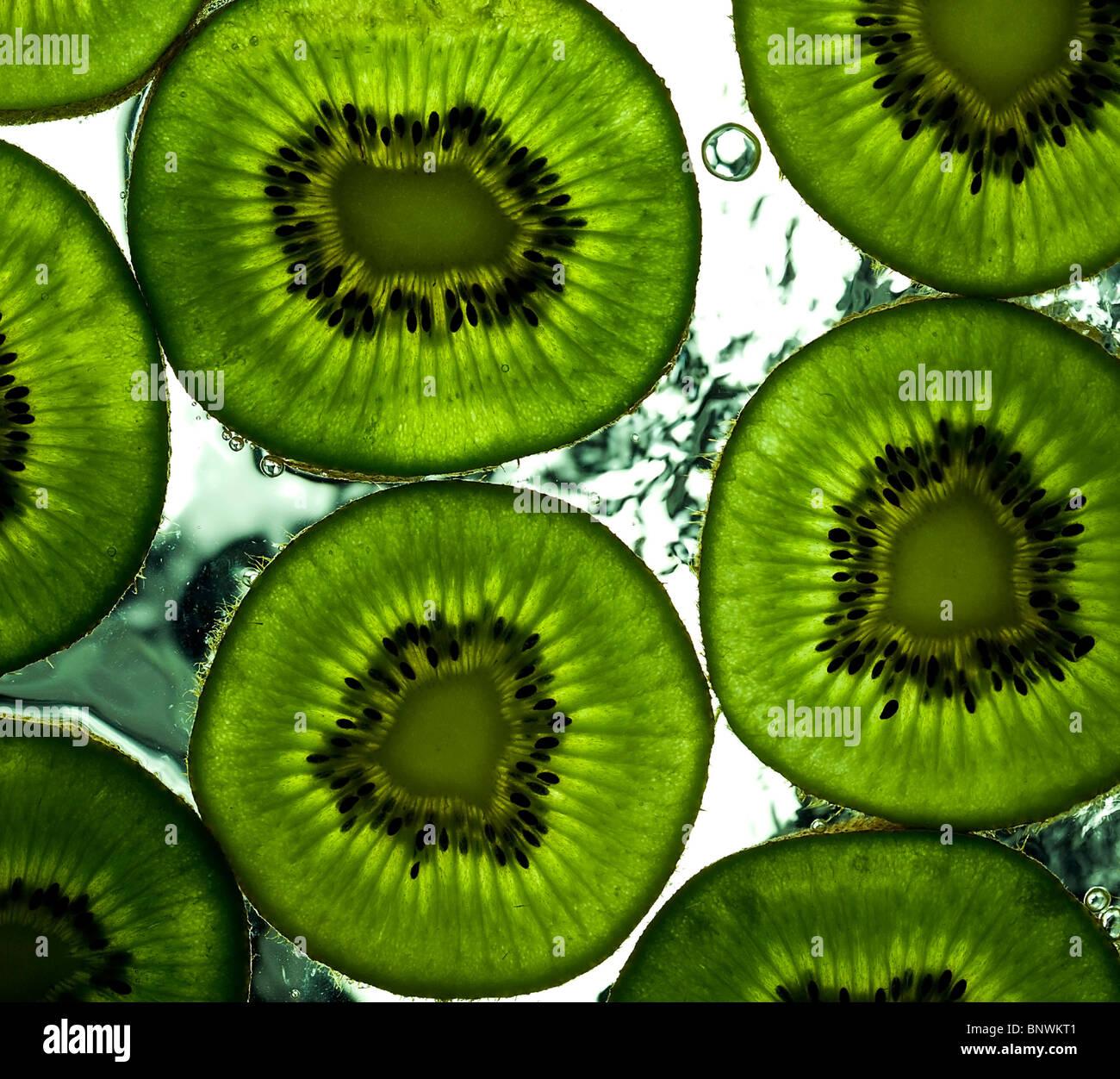 einige Scheiben Reife Kiwi auf der nassen Oberfläche Stockbild