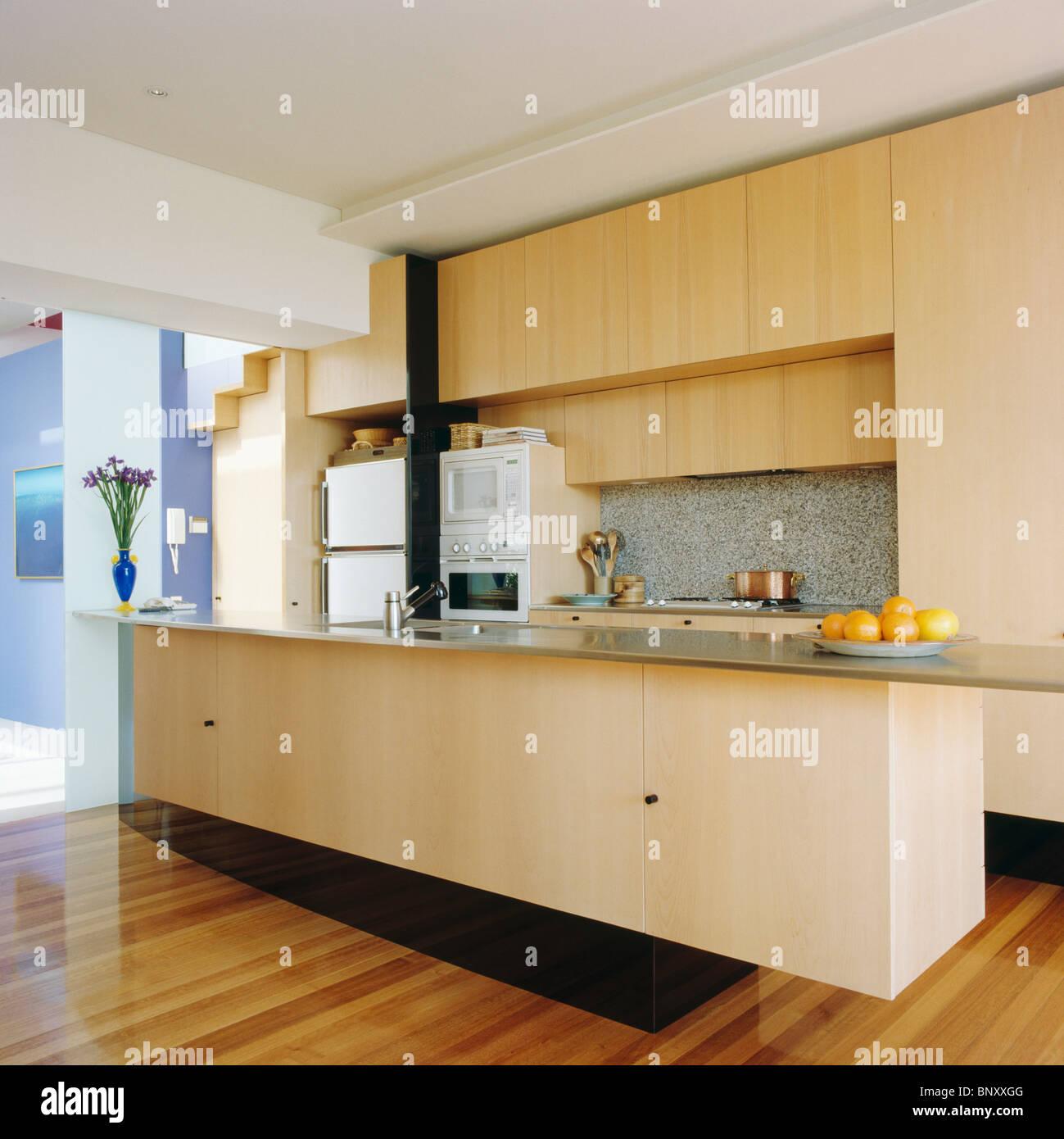 Moderne küchen mit halbinsel  Hellem Holz ausgestattet Einheiten und Holzböden in Verlängerung der ...