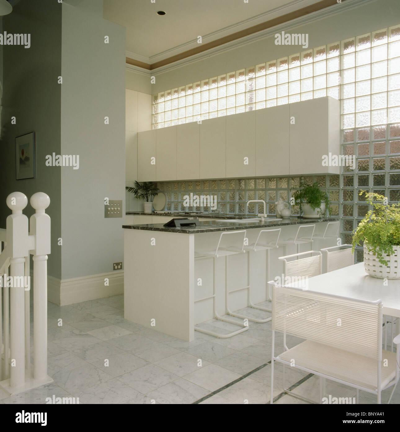 Glasbaustein-Wand in moderne Küche Esszimmer mit weißen Stühlen am ...