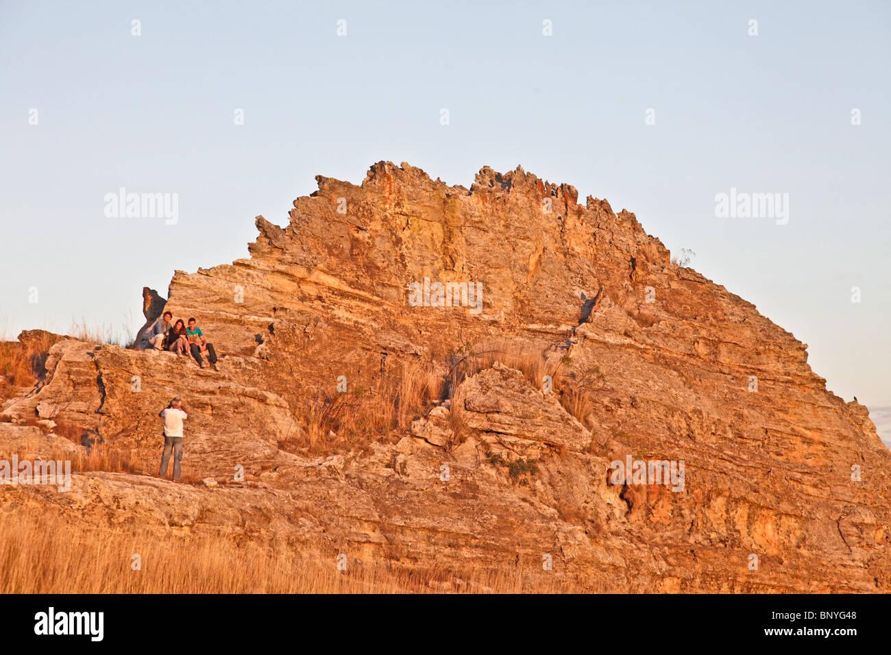 Mann ein Bild von einer Gruppe von Menschen gegen eine sandtone massiv bei Sonnenuntergang in der Nähe der Stockbild