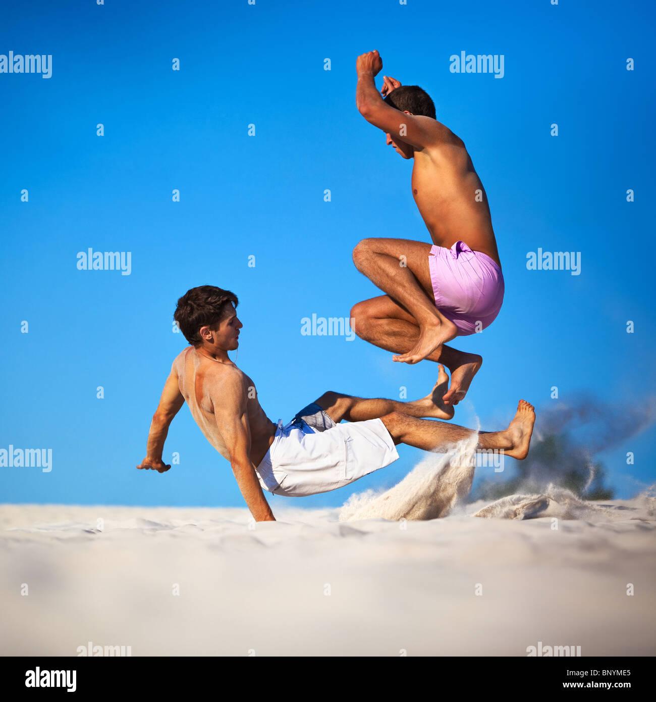 Zwei junge Männer Sport kämpfen am Strand. Stockbild