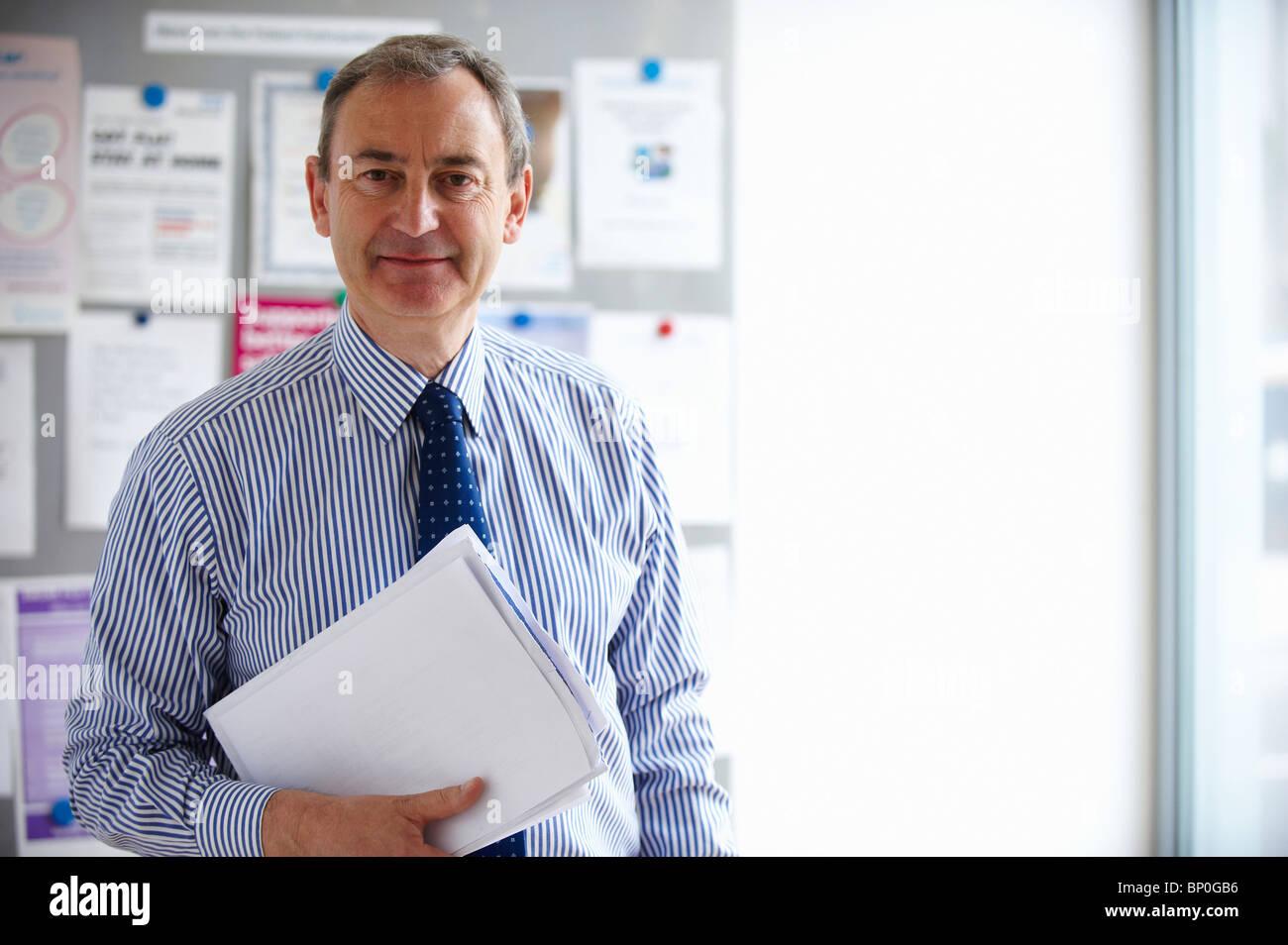 Männlichen medizinischen Berater halten Papiere Stockbild