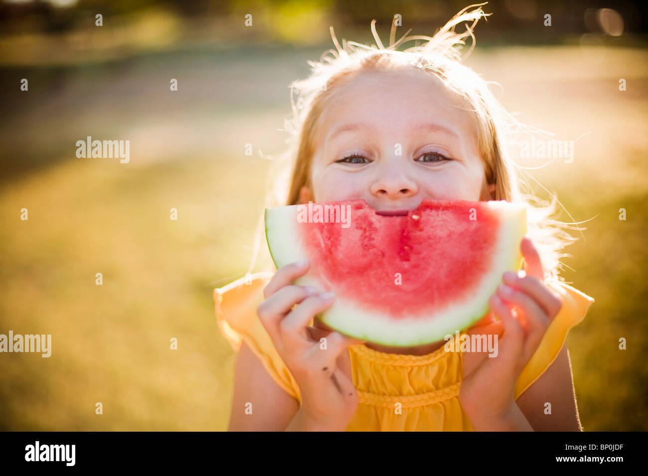 Junge Mädchen machen Lächeln mit Wassermelone Stockbild