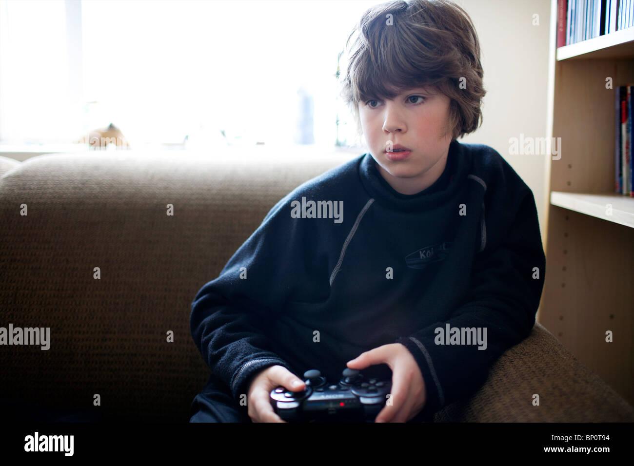 ein kleiner junge auf einer playstation spielen stockfoto. Black Bedroom Furniture Sets. Home Design Ideas
