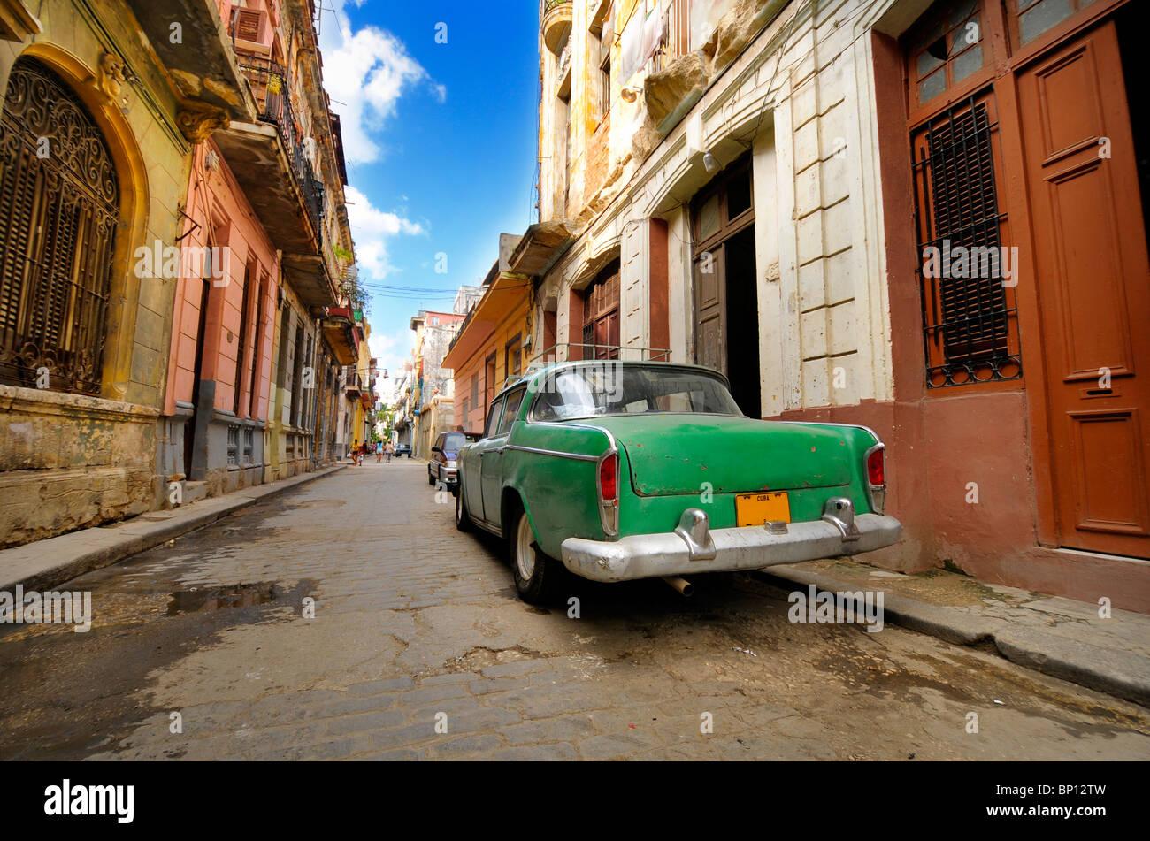 Oldtimer in schäbigen alten Havanna street mit bröckelnden Fassaden geparkt Stockbild