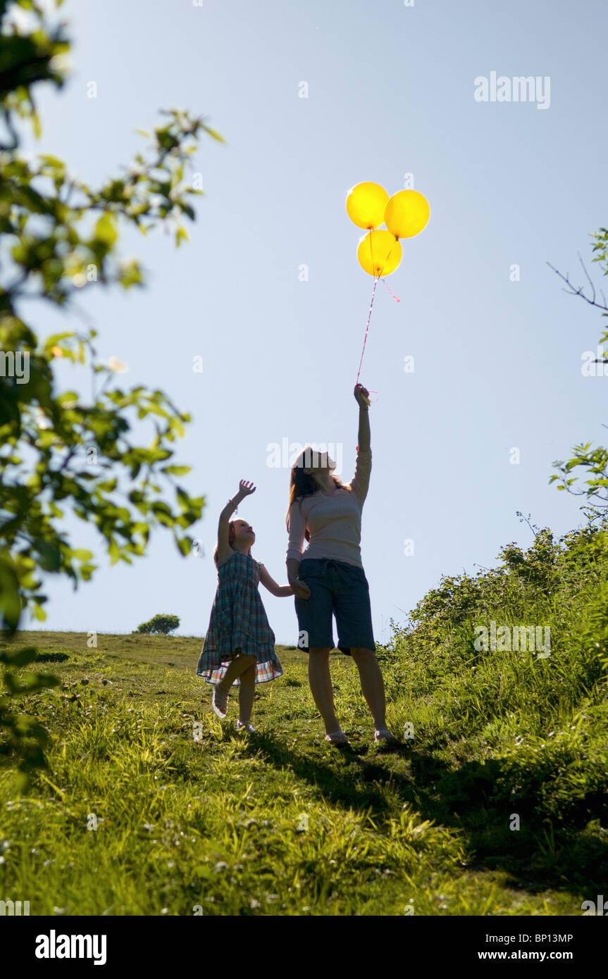Frau und Kind sehen Ballons Stockbild