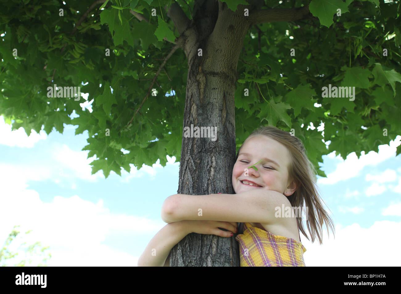 Mädchen umarmt Ahornbaum Stockbild
