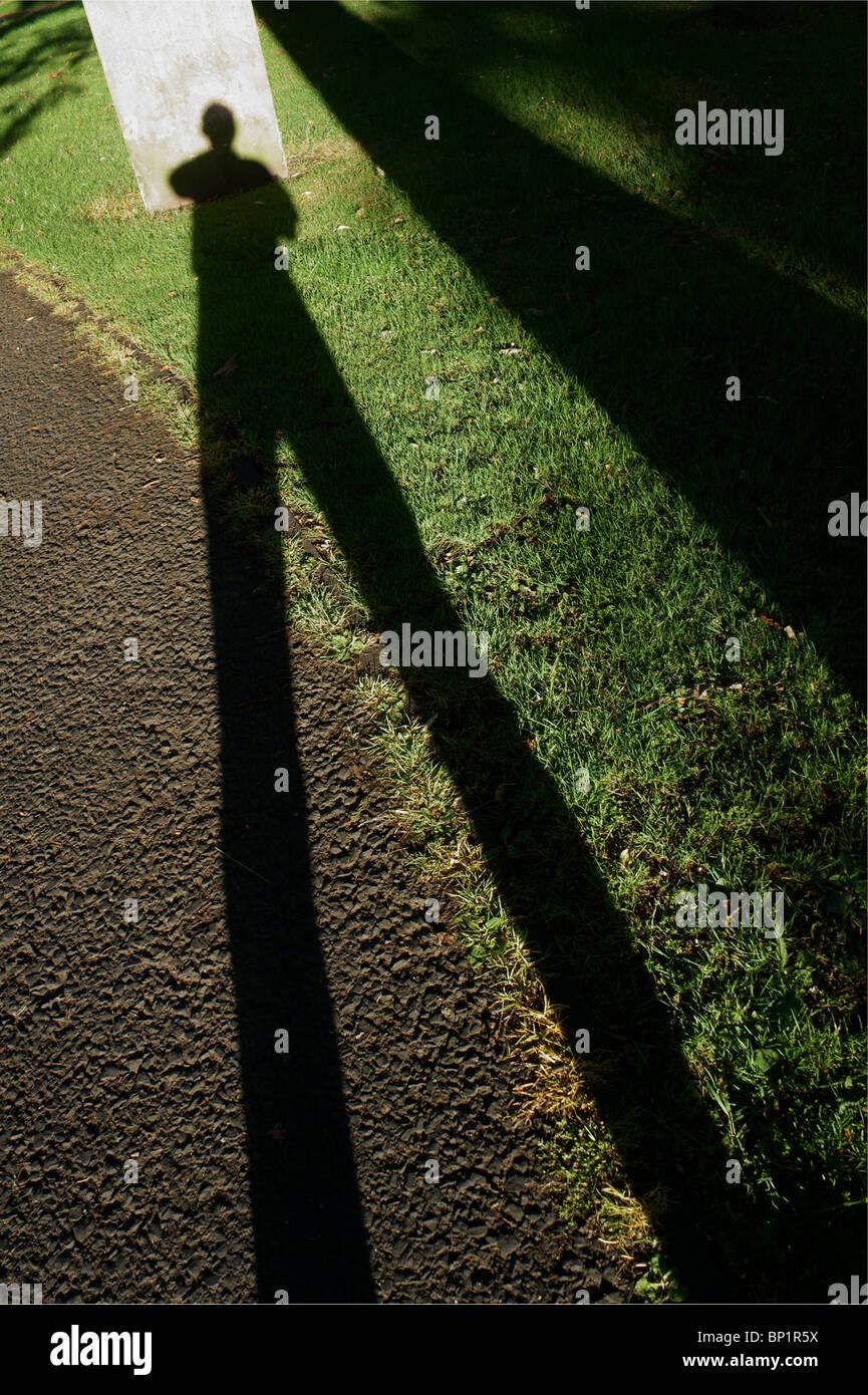 Einen langen Schatten auf einem Grab Stockbild