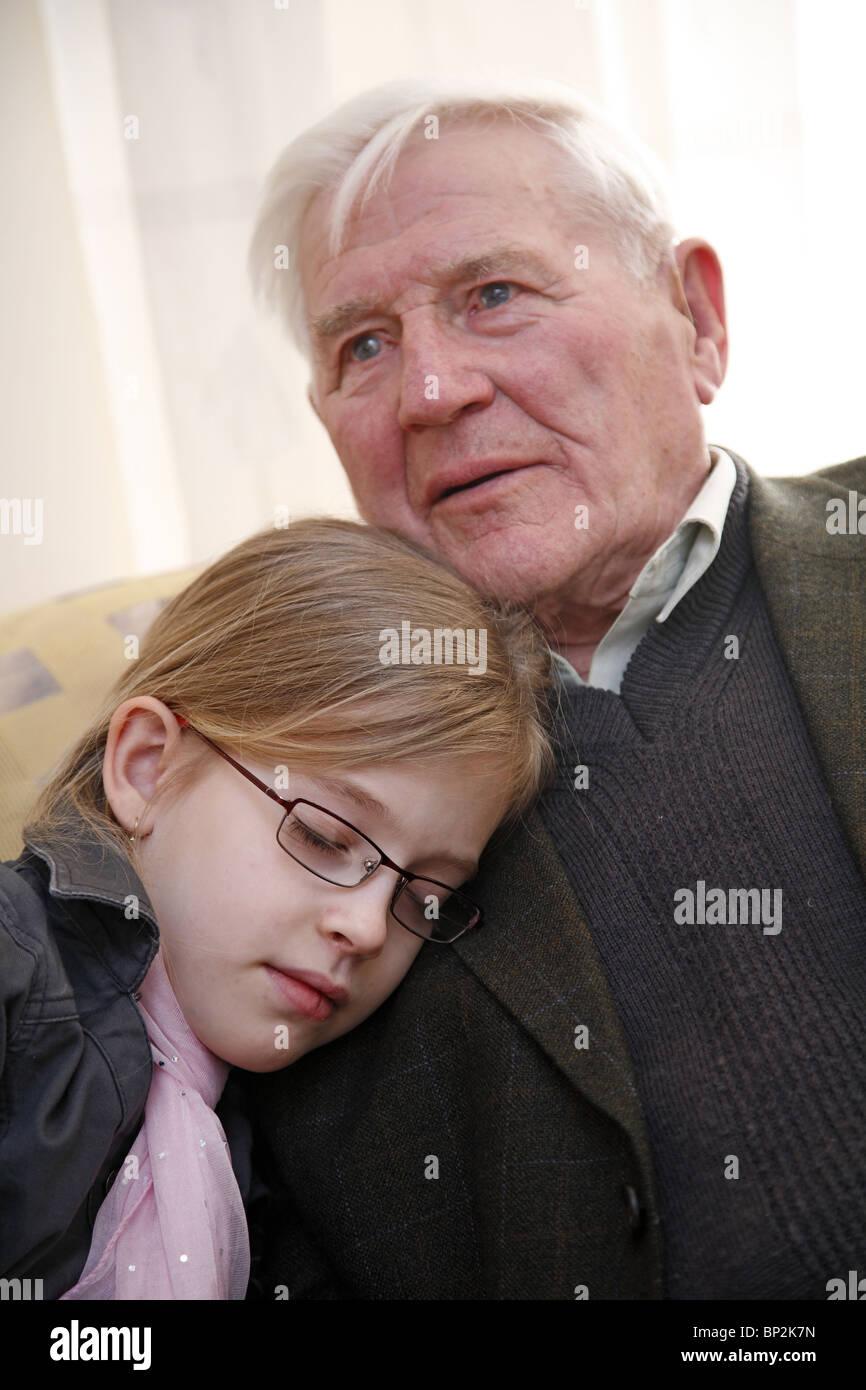 Enkelin zu ihrem Großvater kuscheln Stockfoto