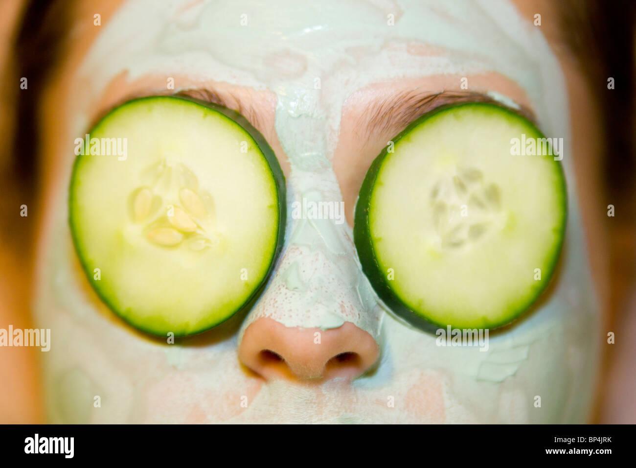Mädchen mit grünen Gesichtsmaske und Gurkenscheiben über Augen Stockbild