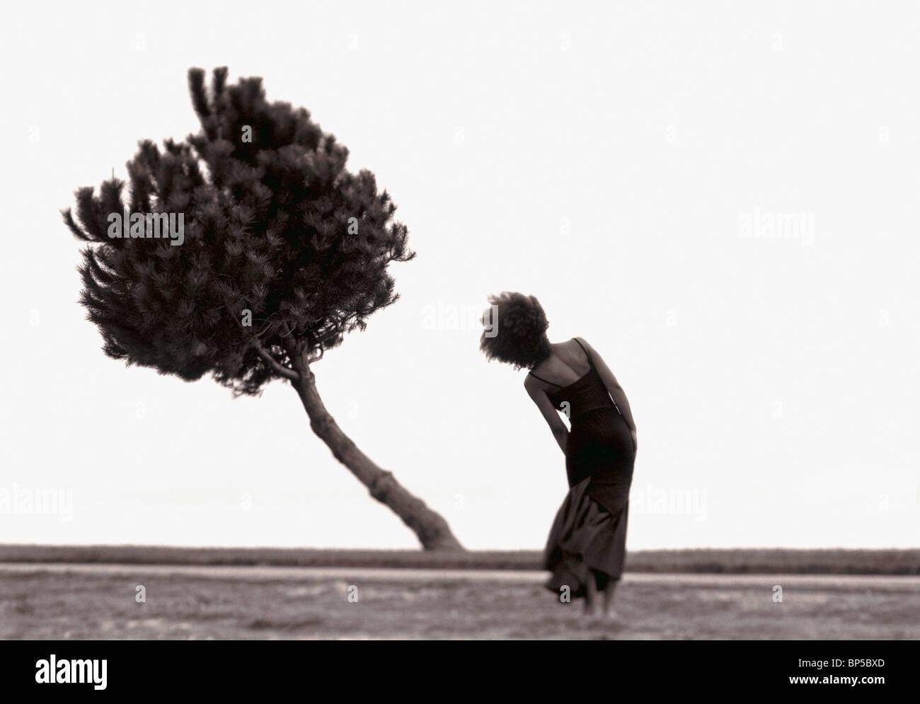 Frau in Landschaft Körper biegen biegen Baum zu imitieren. Stockbild