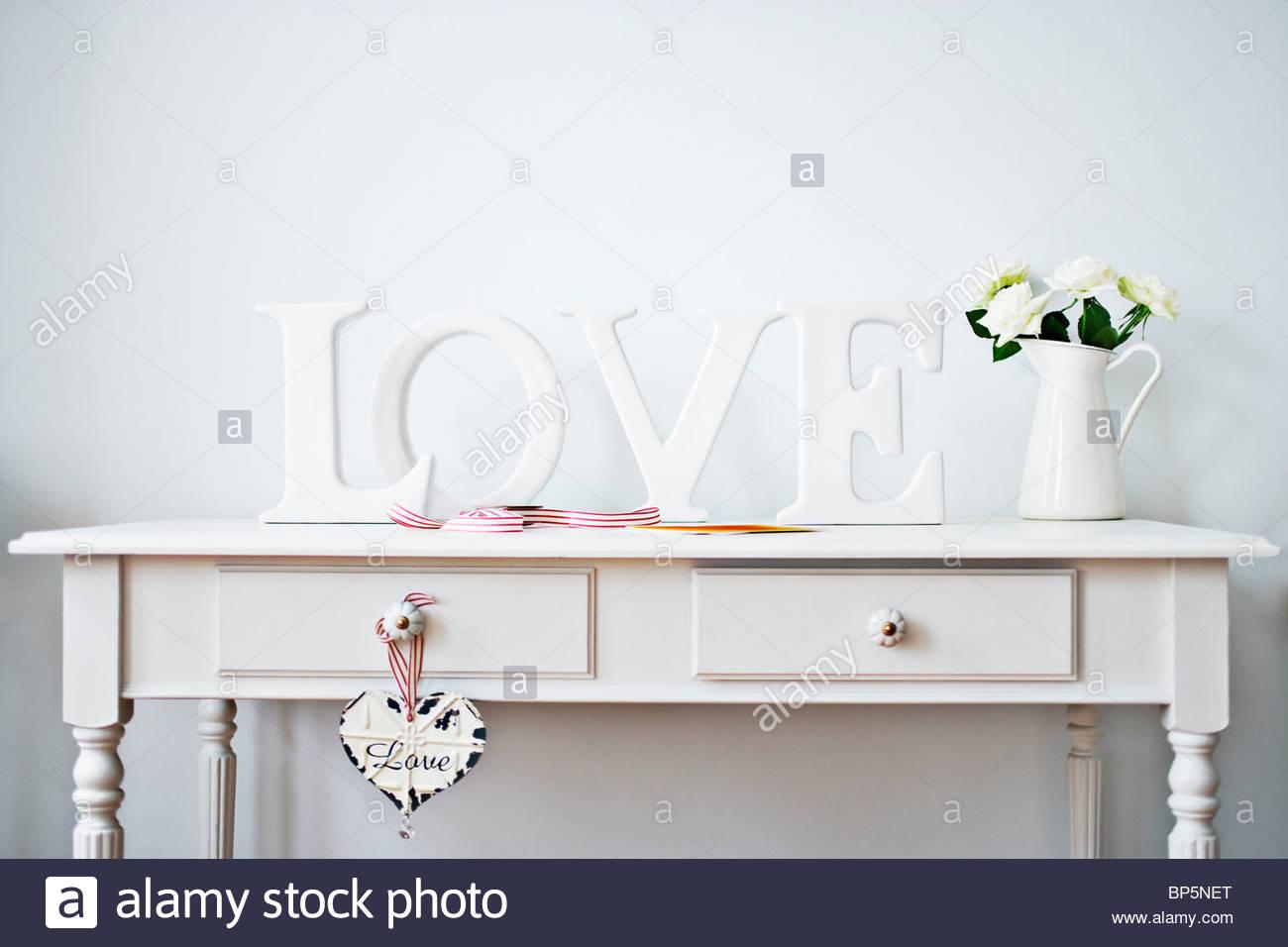"""""""Liebe"""", Dekoration, Band, Rosen und Karte auf Schreibtisch Stockbild"""