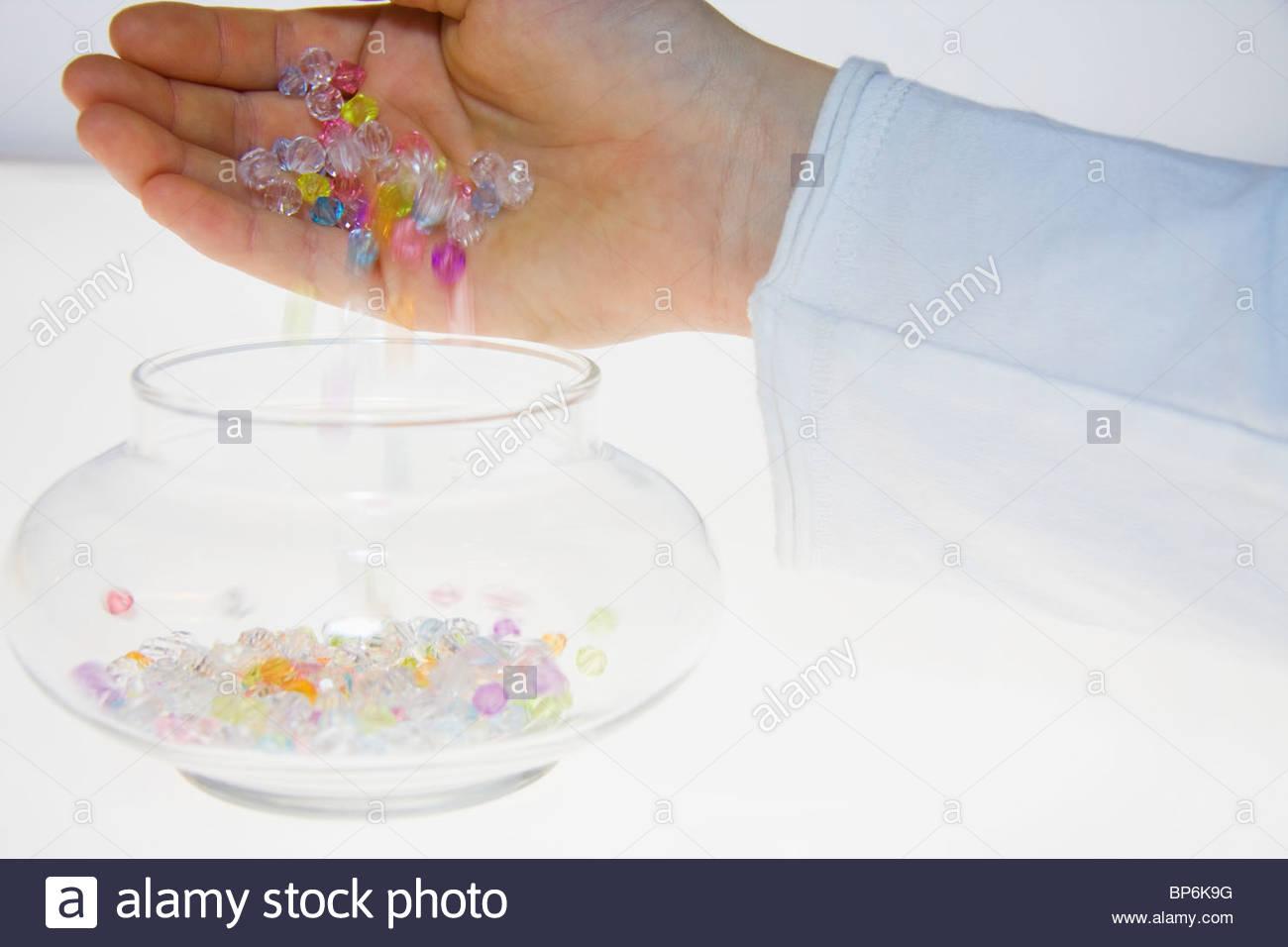 Eine Person, die bunte Perlen in ein Glas gießen Stockbild