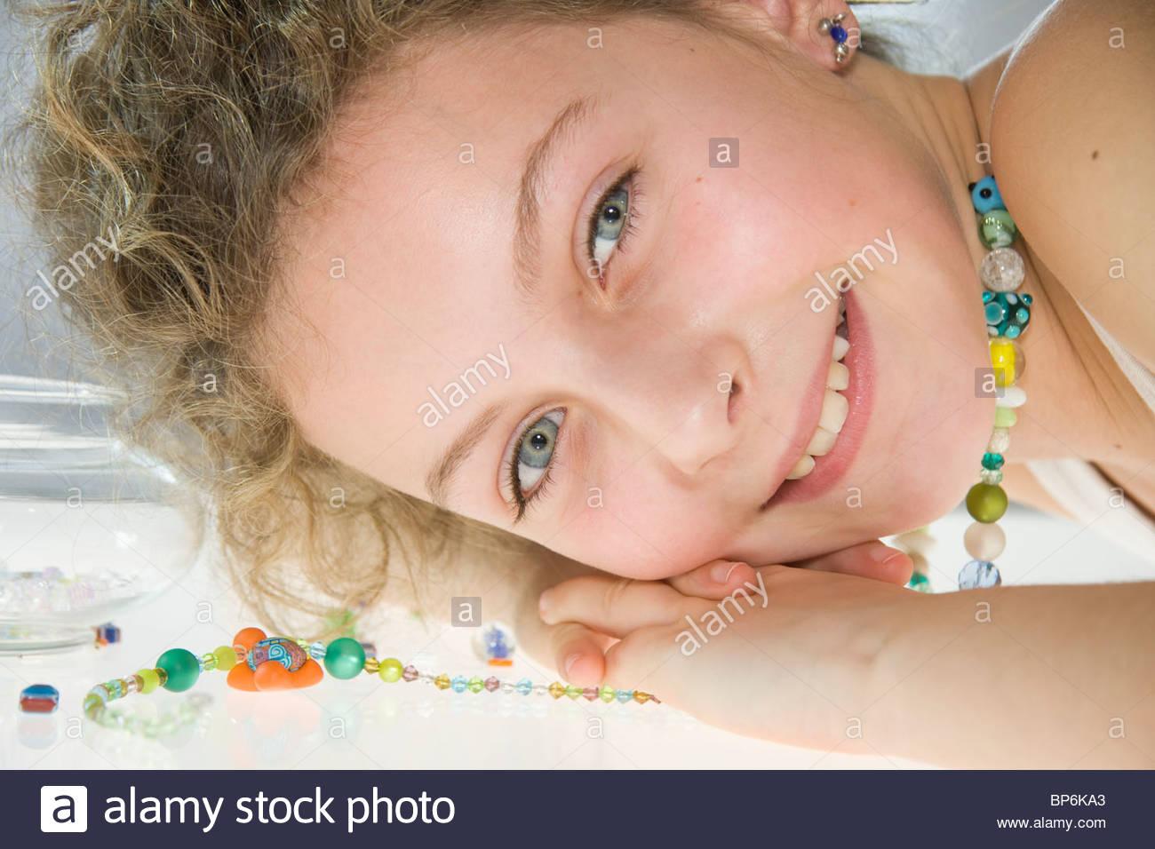 Ein junges Mädchen tragen eine handgemachte Halskette, Gesicht ruhen auf einem Tisch Stockbild