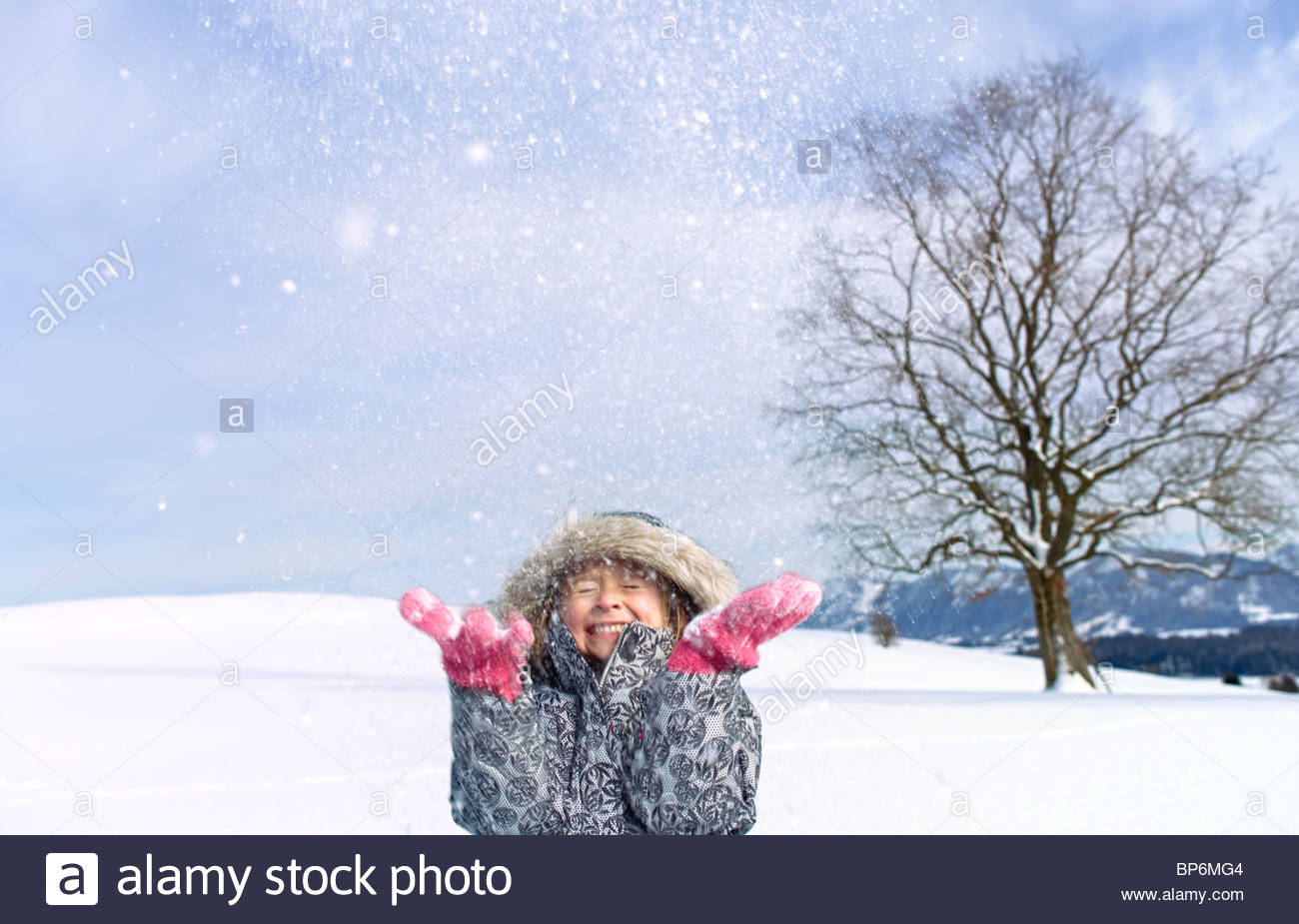 Fröhliches junges Mädchen wirft Schnee in der Luft Stockbild