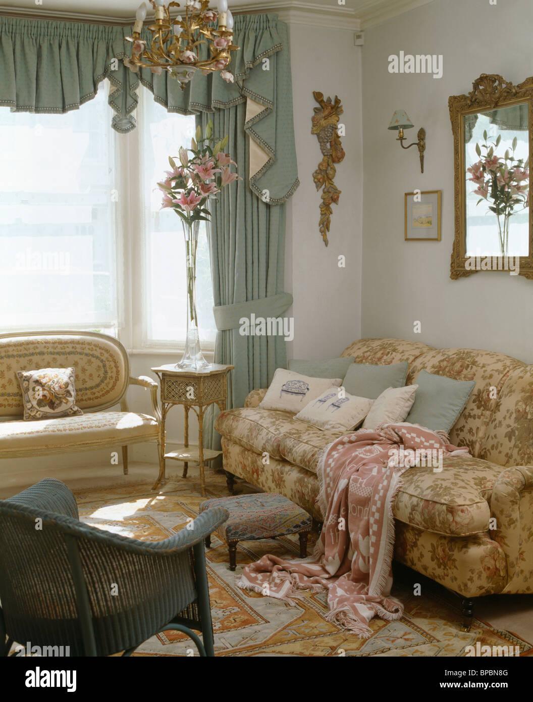 Pastell Grün Swagged Vorhänge Am Fenster Im Wohnzimmer Mit Gemusterten Wurf  Auf Bequemen Sofa