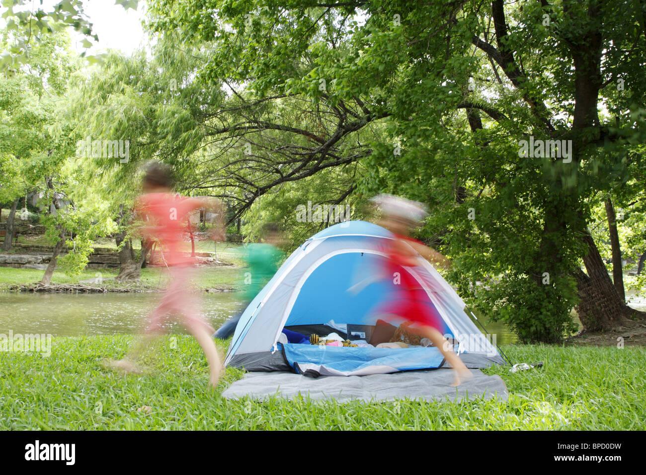 Kinder jagen einander um ein Zelt beim camping Stockfoto