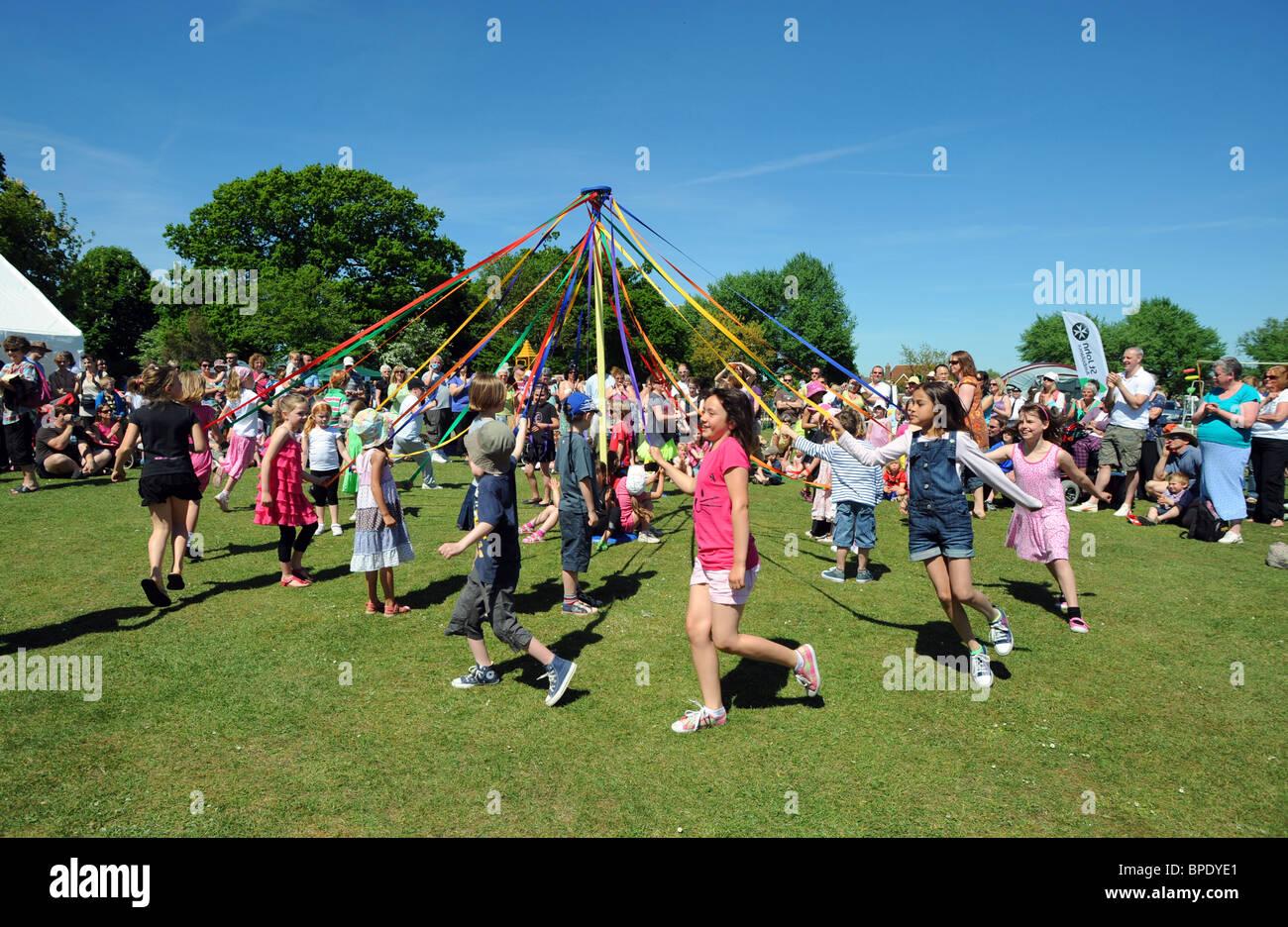 Junge Kindertanz runden ein Maibaum bei einem Dorffest in Rigmer in Sussex Stockbild