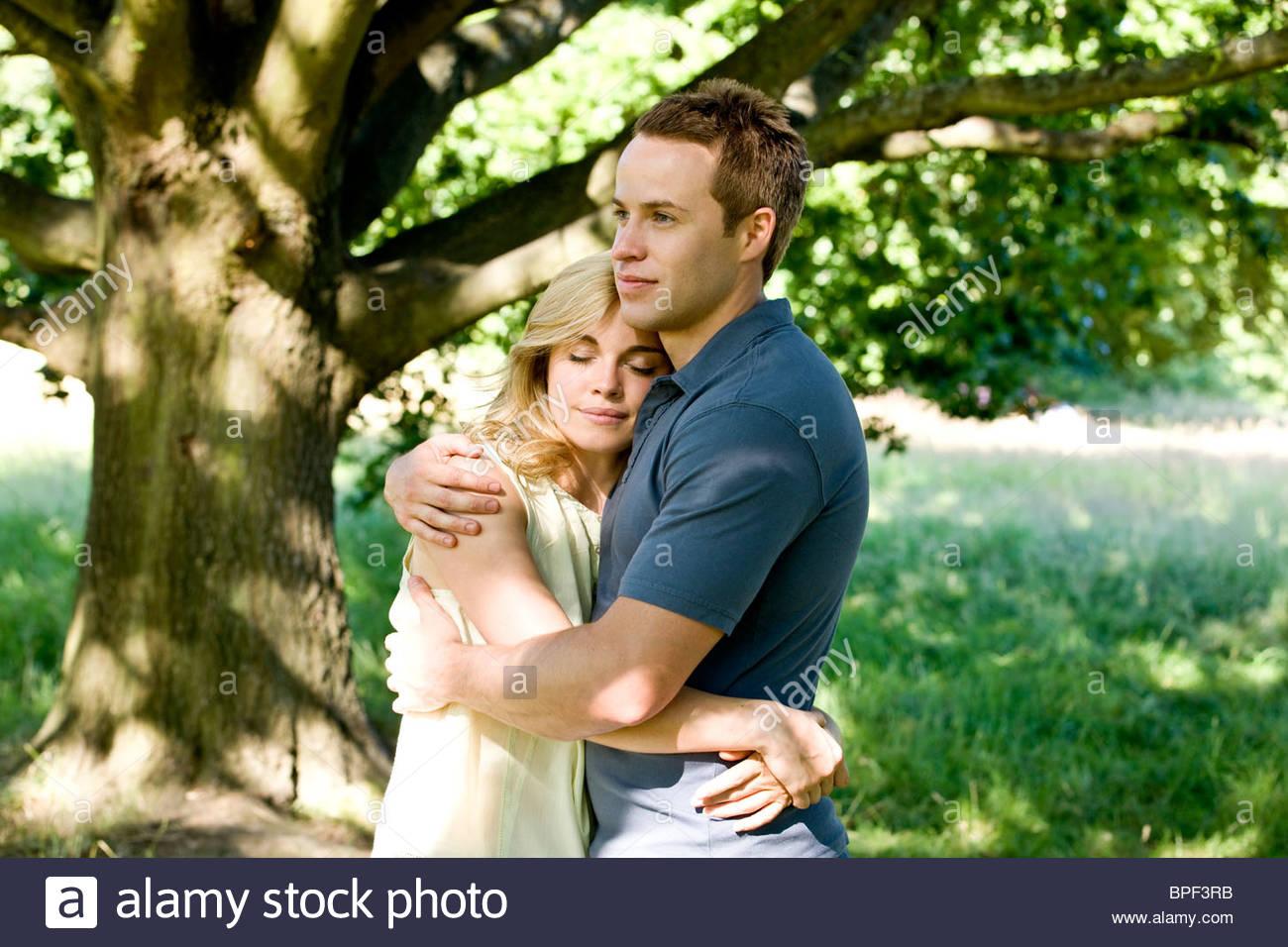Ein junges Paar steht unter einem Baum umarmen Stockbild