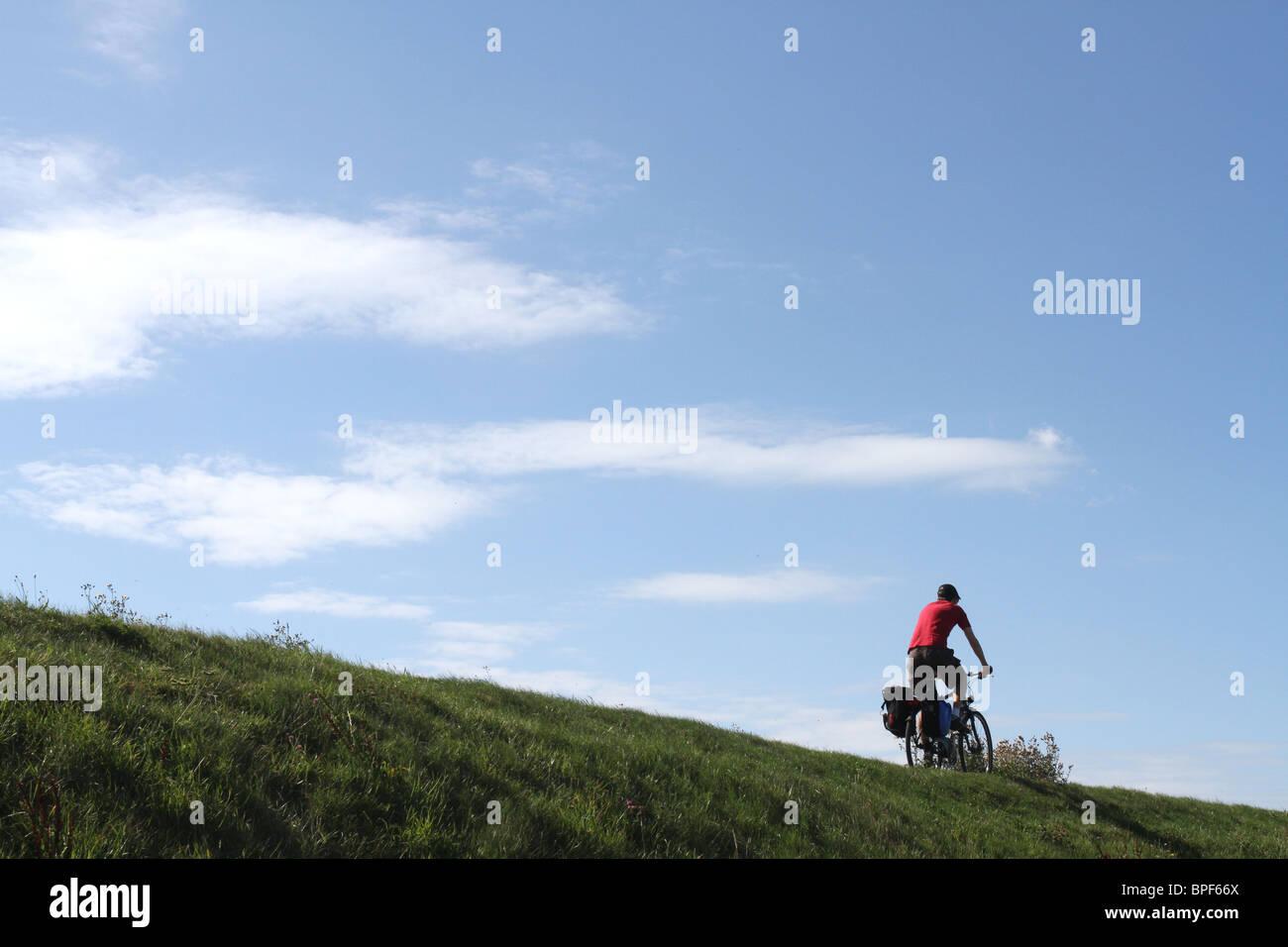 Mann oben auf einem Felsvorsprung Grass Radfahren Stockbild