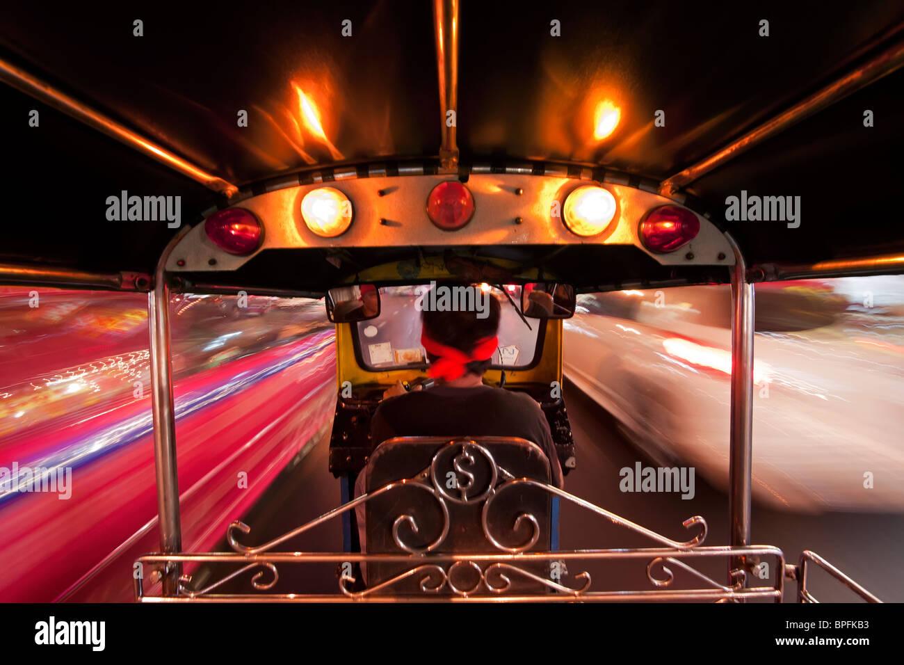 Tuk Tuk oder Auto-Rikscha in Bewegung bei Nacht, Bangkok, Thailand, Südostasien Stockbild