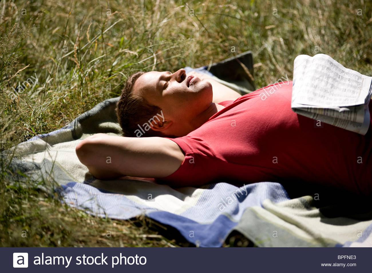Ein junger Mann in der Sonne liegen Stockbild