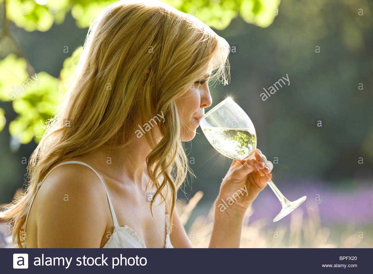 Eine junge Frau trinkt ein Glas Weißwein Stockbild