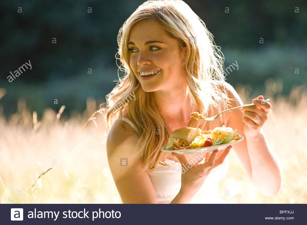 Eine junge Frau auf dem Rasen sitzen, Essen Stockbild