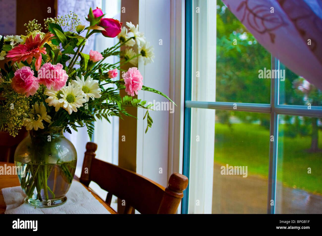 Frische Blumendekoration auf einem Küchentisch Stockbild