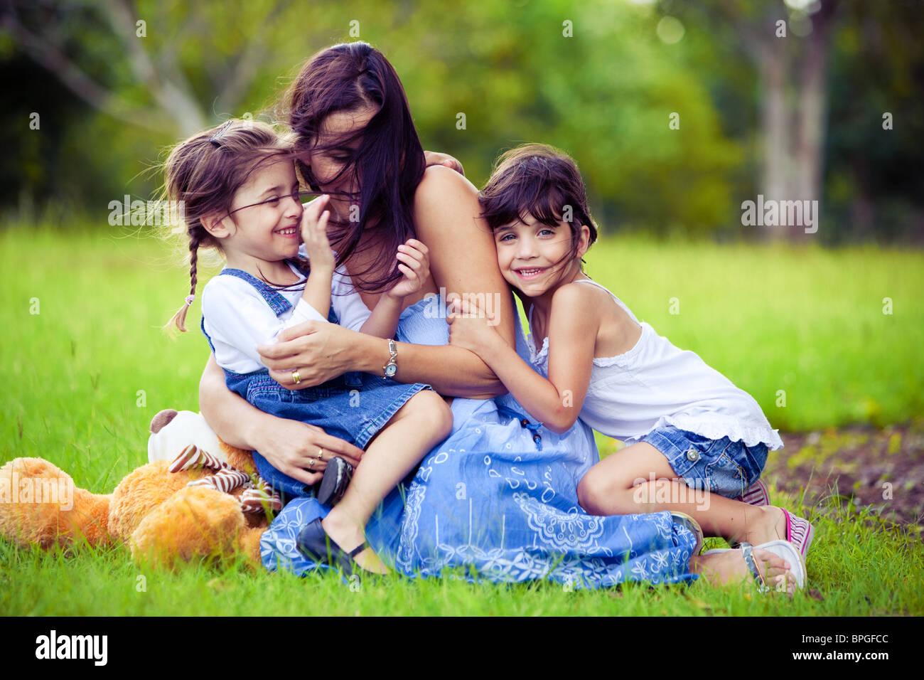 Junge Mutter und zwei Töchter im Rasen spielen Stockbild